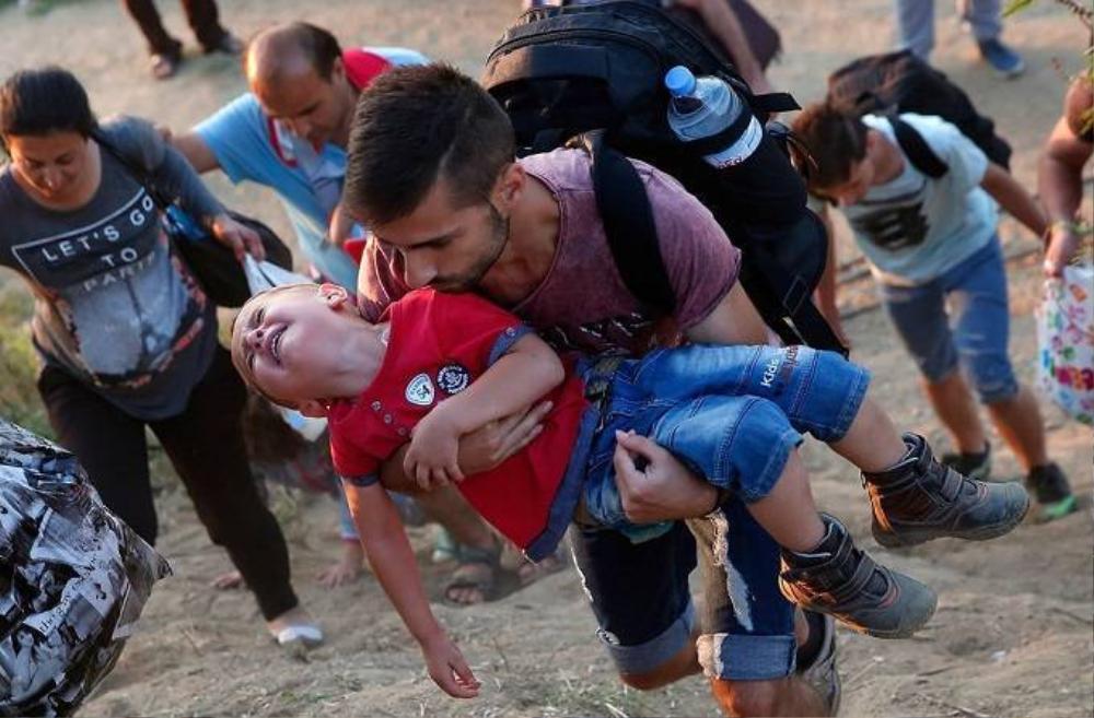 Một cậu bé người Syria khóc lóc khi được cha bồng trên tay khi cả hai đang cố gắng vượt biên giới vào Hy Lạp, ngày 3/9.