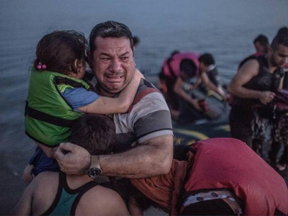 Một người cha ôm gia đình khóc vì tất cả đã an toàn đến được đảo Kos.