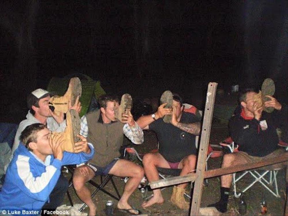 """Thi đua uống cạn """"ly bia giày"""" trong buổi cắm trại."""