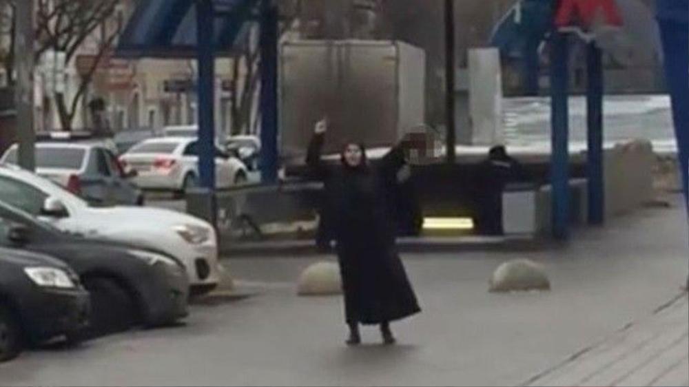 Người phụ nữ giơ cao chiếc đầu trẻ em gần ga tàu điện ngầm. Ảnh: Moscow TV