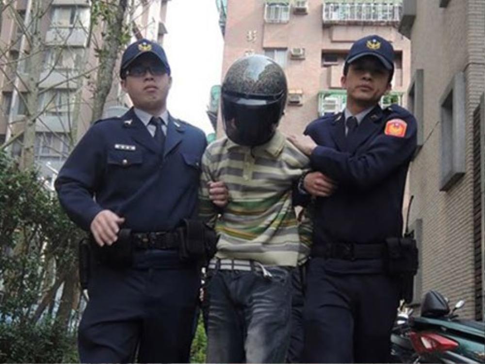 Kẻ tấn công (giữa) bị cảnh sát giải đi.