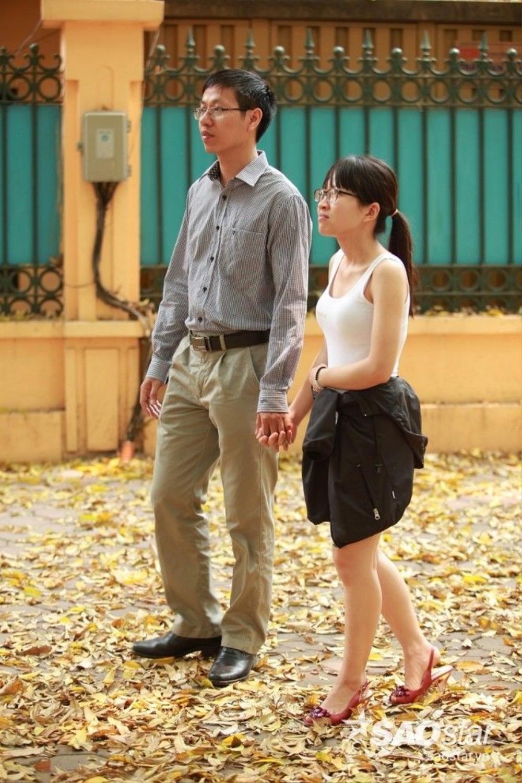 Cặp tình nhân nắm chặt tay nhau đi trên con đường đầy lá.