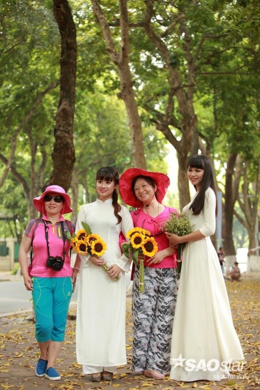 Du khách nước ngoài hồ hởi chụp kỷ niệm cùng tà áo dài Việt Nam.