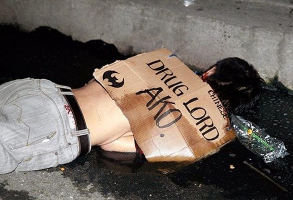 """Tấm bảng ghi chữ """"Tôi là trùm ma túy"""" được úp trên một người bị hành quyết trên phố."""