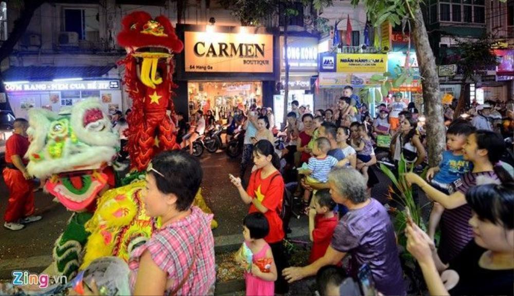 Nhiều người dân hòa chung niềm vui, đi bộ theo đoàn múa lân từ phố này sang phố khác.