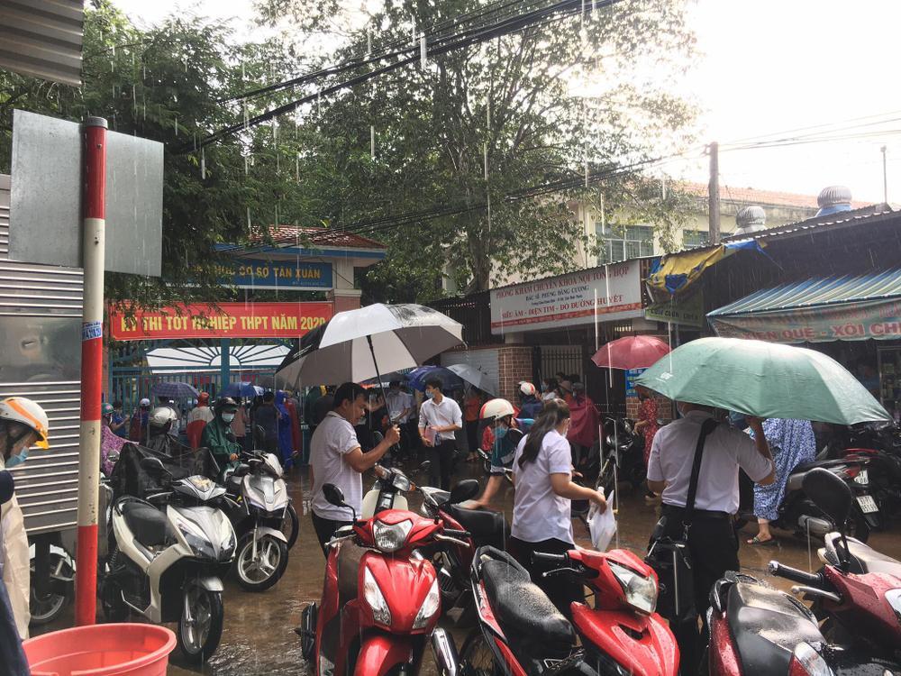 Phụ huynh ở Bình Phước đứng đợi thí sinh dưới cơn mưa lớn trong buổi thi Toán chiều nay Ảnh 1