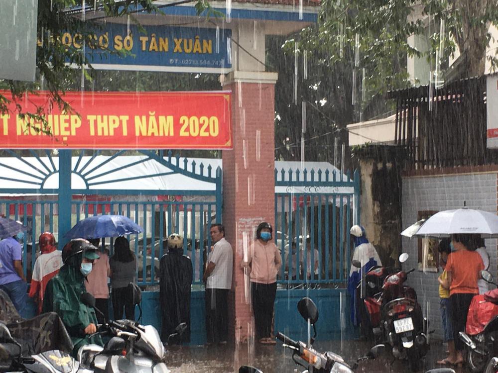Phụ huynh ở Bình Phước đứng đợi thí sinh dưới cơn mưa lớn trong buổi thi Toán chiều nay Ảnh 2