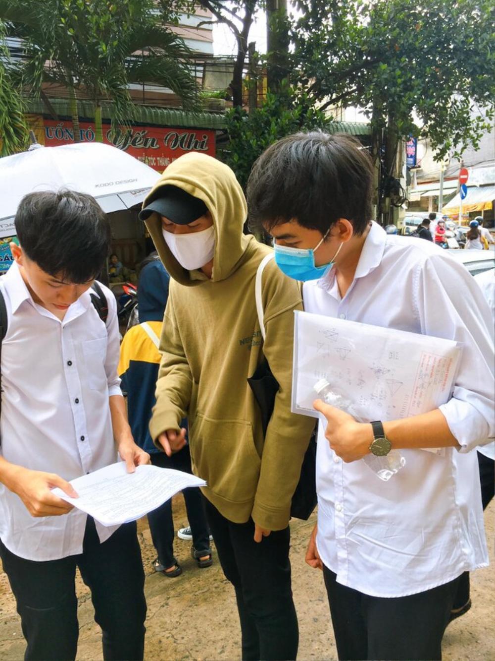 Phụ huynh ở Bình Phước đứng đợi thí sinh dưới cơn mưa lớn trong buổi thi Toán chiều nay Ảnh 9