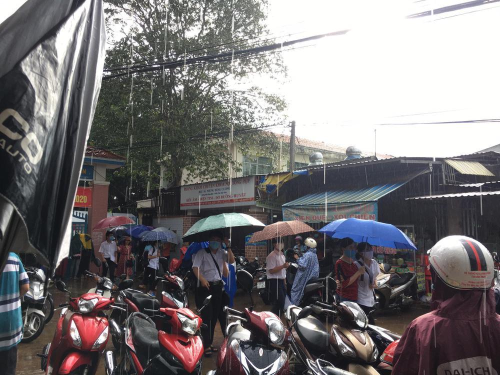 Phụ huynh ở Bình Phước đứng đợi thí sinh dưới cơn mưa lớn trong buổi thi Toán chiều nay Ảnh 3