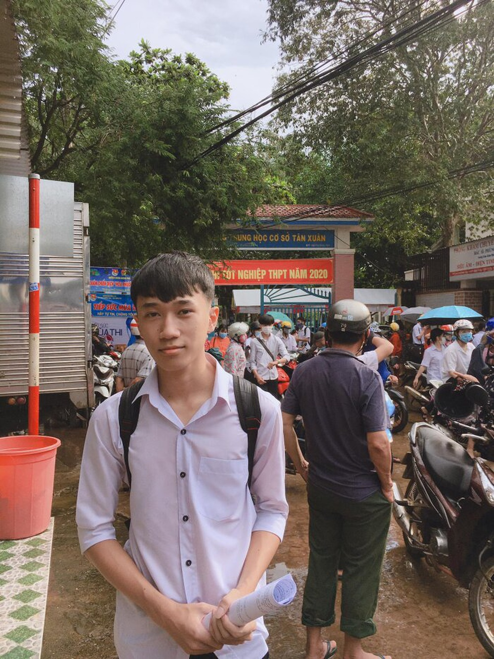 Phụ huynh ở Bình Phước đứng đợi thí sinh dưới cơn mưa lớn trong buổi thi Toán chiều nay Ảnh 8