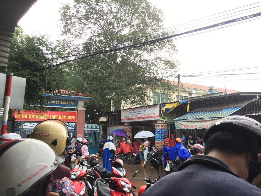 Phụ huynh ở Bình Phước đứng đợi thí sinh dưới cơn mưa lớn trong buổi thi Toán chiều nay Ảnh 6