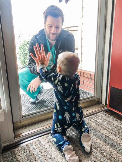 Bác sĩ Jared chạm tay con trai qua lớp cửa kính.