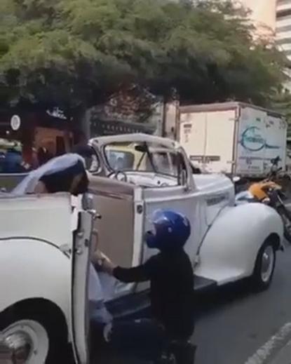 Người đàn ông bám vào xe cưới và quỳ xuống van xin cô dâu. Ảnh: CEN