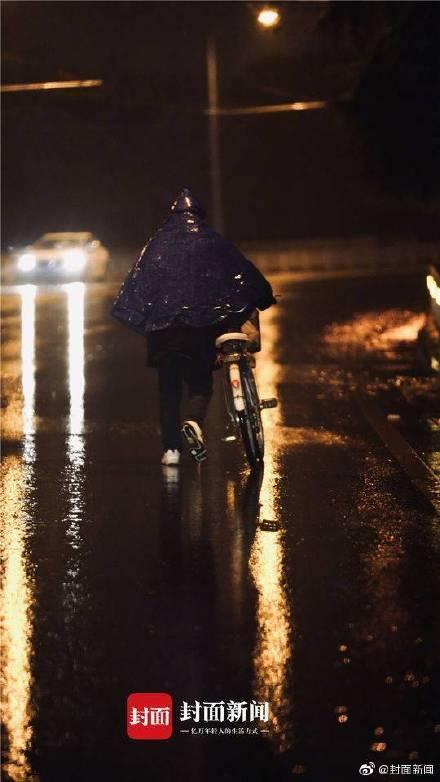 Một người dân dắt xe đạp đi bộ dưới mưa trong đêm giao thừa. Ảnh Weibo