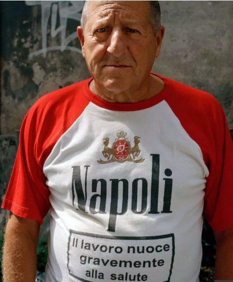 Một người đàn ông đứng tuổi tại Napoli và chiếc áo thú vị có chữ Làm việc có hại cho sức khỏe