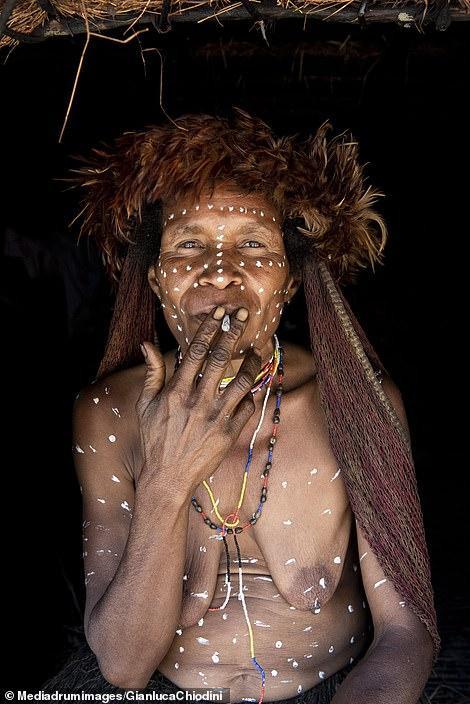 Một người phụ nữ Dani đang hút thuốc với cơ thể được vẽ sơn trắng