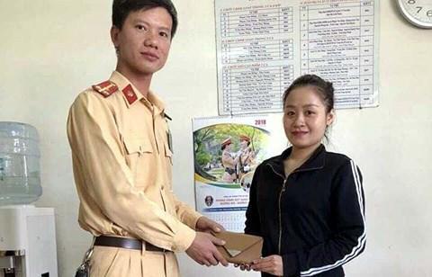 Chiến sĩ CSGT trao ví cho cô gái.