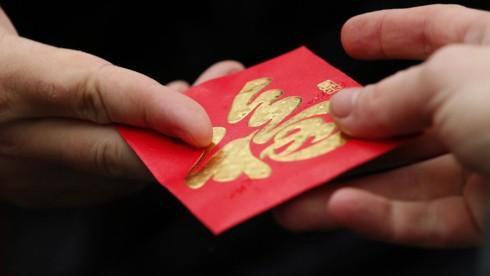 Trong dịp Tết, mọi người gửi tặng nhau phong bao lì xì mừng tuổi và không quên nói những lời may mắn, tốt đẹp. Ảnh: KT.