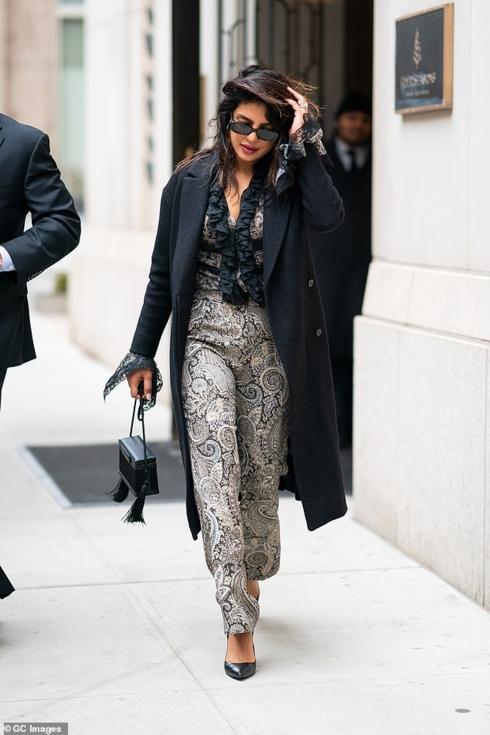 Mái tóc rối cùng trang phục jumpsuit thổ cẩm trên mình, diện hờ áo khoác đen ở ngoài sải bước tự tin trên phố
