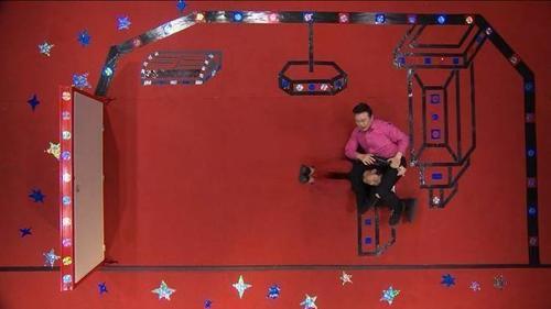 """Ở thử thách sân khấu nằm, Trấn Thành và Chí Tài phải ứng biến trên con tàu vũ trụ. Cả 2 đều rơi vào trạng thái không trọng lực và giọng ca Nhỏ ơi có dịp """"bắt nạt"""" đàn em bằng việc đè Trấn Thành bằng thân hình """"phì nhiêu"""" của anh."""