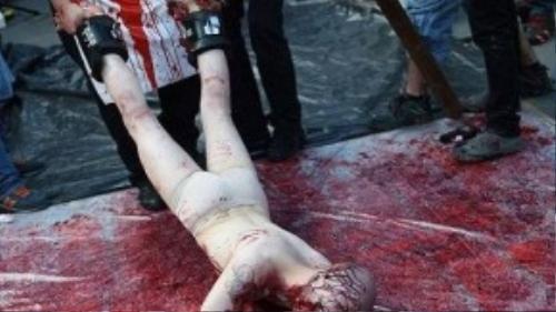 Một người tình nguyện bị kéo lê trên nền đất nhuốm đầy máu giả.