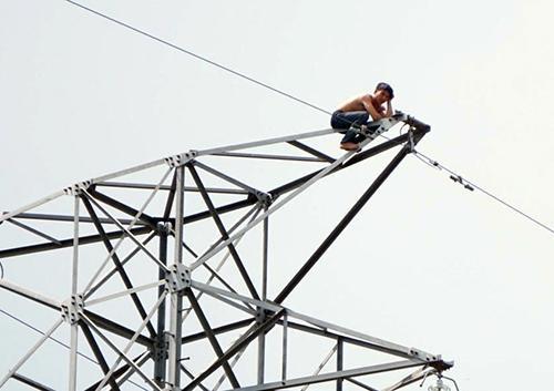 Nam thanh niên leo lên đỉnh trụ điện 220kV. Ảnh: Nguyệt Triều.