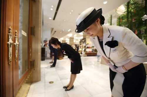 Nhân viên tại một trung tâm thương mại cúi chào khách hàng. Ảnh: Japan Times.