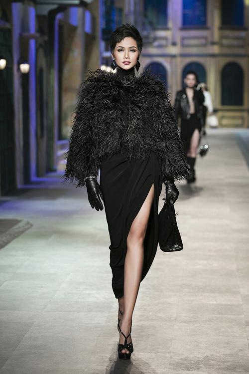 Người đẹp 26 tuổi sải những bước chân đầu tiên khuấy động không khí sàn diễn với bộ trang phục lấy sắc đen làm chủ đạo, kết hợp giữa chân váy xẻ tà bất đối xứng cùng áo cổ lọ, áo khoác lông.