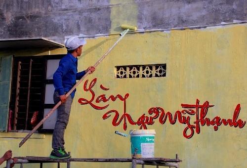 Nhóm bạn trẻ quét sơn lên tường nhà ở làng Ngư Mỹ Thạnh. Ảnh: Võ Thạnh