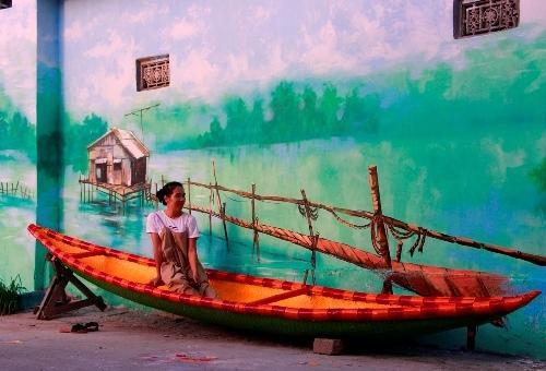 Một bạn trẻ tạo dáng bên một bức tường tranh ở làng Ngư Mỹ Thạnh. Ảnh: Võ Thạnh
