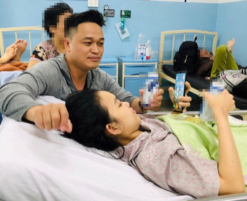 Anh Lê Văn Nam chăm sóc Thuỳ Dương trong bệnh viện. (Ảnh: Thanh Niên)