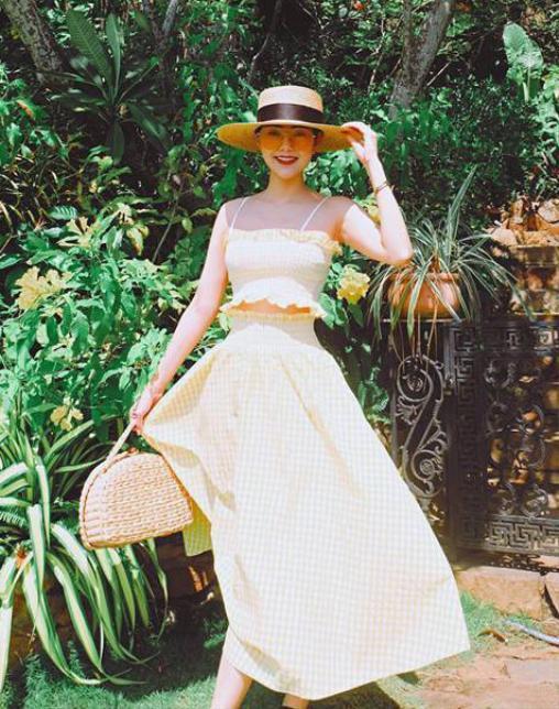 """Minh Hằng đúng chất """"cô gái mùa hè"""" khi diện tone vàng rực rỡ phối hợp với túi và mũ cói. Chất """"thiên nhiên"""" của đồ cói giúp cô trông khỏe khoắn, giàu sức sống."""