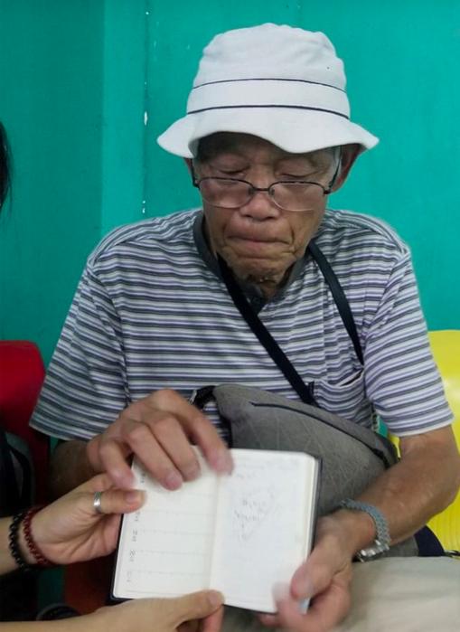 Cụ Oki cho PV xem cuốn nhật ký du lịch, mỗi ngày cụ đều ghi lại hành trình và chi phí. Ảnh: báo Thanh Niên.