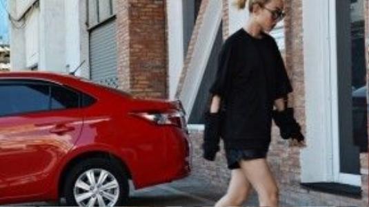 Cô nàng diện áo sweater cut-out độc đáo ở phần tay phối cùng short da và giày bốt cá tính.