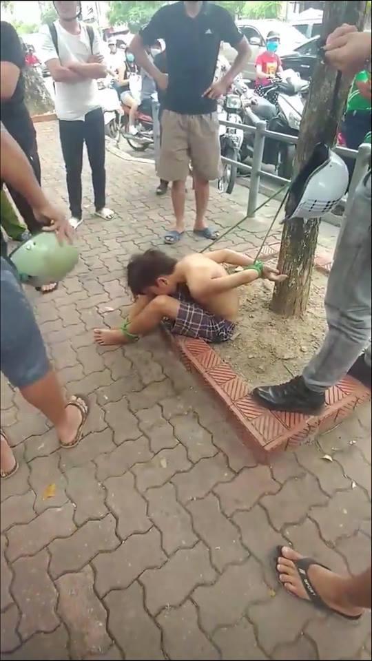 Hình ảnh cậu bé bị trói hai chân tay gây xôn xao.