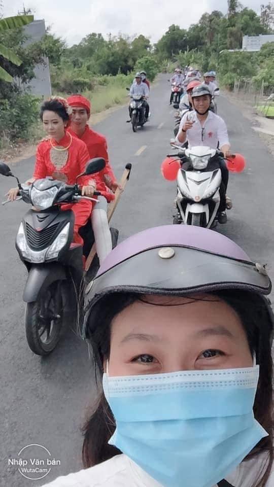 Cô dâu lái xe chở chú rể cùng quan viên hai họ trên đường làng.