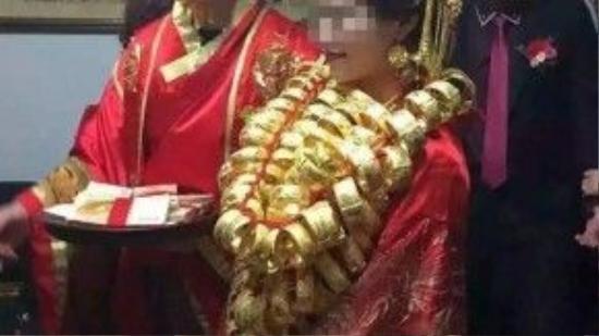 Chú rể cùng cô dâu đeo vàng đầy người lúc làm lễ.