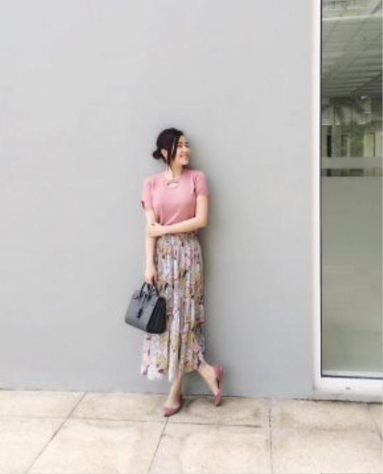 Cô nàng lại biến hóa bản thân với phong cách nữ tính cùng tông màu chủ đạo là sắc hồng pastel. Chân váy Pleat họa tiết được hòa phối khéo léo bằng sự trùng lập màu sắc giữa áo T-shirt và giày bệt nhẹ nhàng.