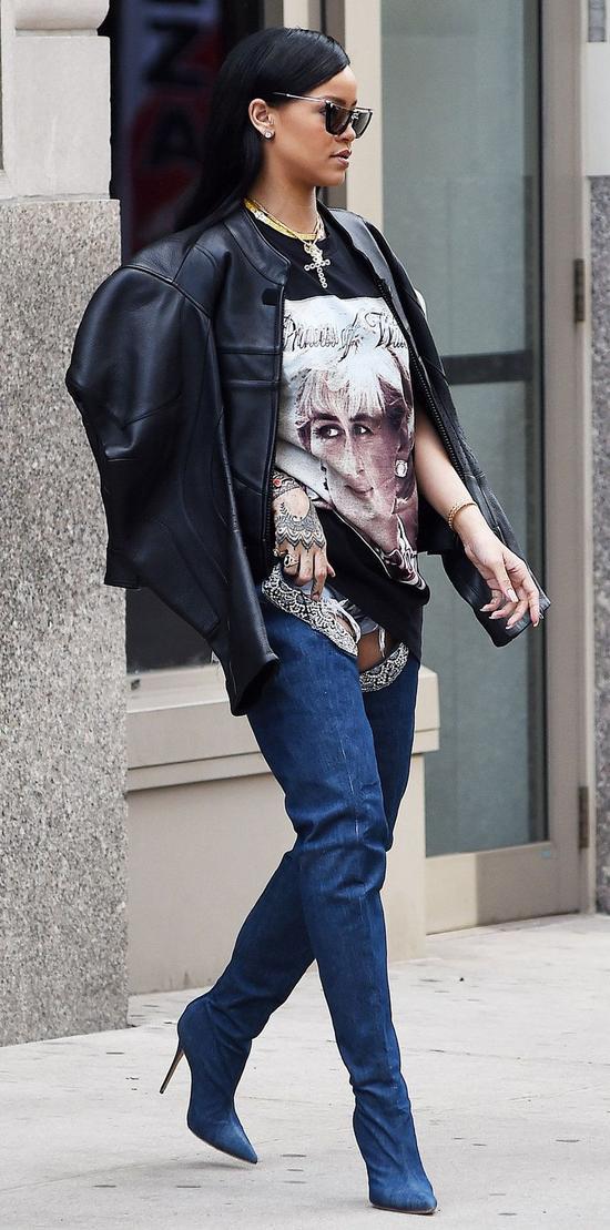 """Không còn gì có thể bàn cãi vì độ """"cool"""" và phá cách trong việc mix-match trang phục của nữ ca sĩ Rihanna. Cô hoàn toàn gây ấn tượng nhờ set đồ kết hợp giữa chiếc áo khoác da tay phồng, áo thun dáng dài và điểm đặc biệt đến từ đôi boot cao cổ mang chất liệu denim."""