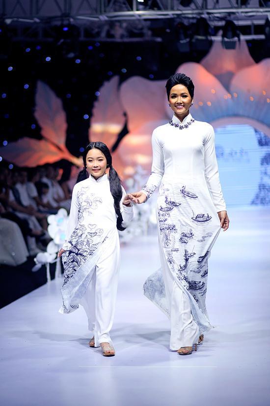 H'Hen Niê xuất hiện ở cuối show trong hình ảnh cô giáo làng. Hoa hậu sải bước catwalk chậm rãi cùng một cô bé người mẫu.