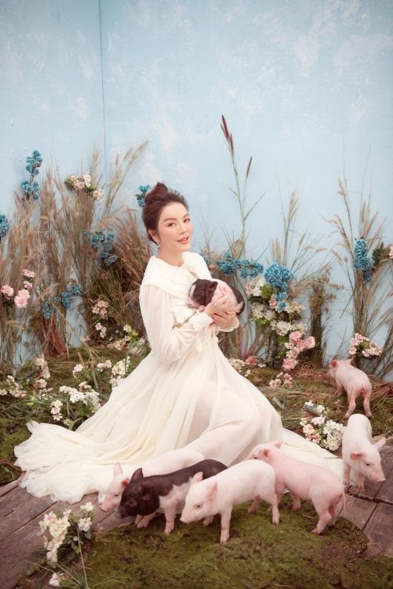 Diện bộ váy trắng thanh tao, người đẹp không ngại ngồi xổm, ôm các chú lợn chụp ảnh.