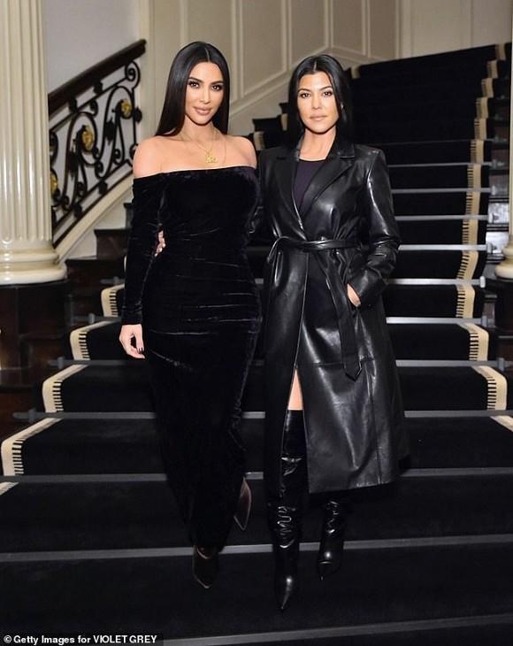 Kim Kardashian trong chiếc váy đen nhung kín đáo còn chị gái Kourtney chọn trang phục áo măng tô da dáng dài mix cùng boots cao cổ