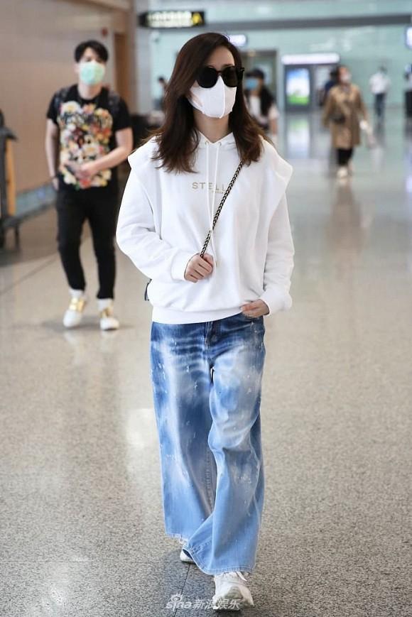 Hình ảnh mới đây nhất với style vô cùng hip hop khi Xa Thi Mạn chọn áo trắng hoodie mix cùng quần denim rộng thùng thình sải bước ngoài sân bay