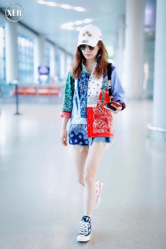 Kiểu áo sơ mi khá nam tính hơi hướng unisex họa tiết đặc biệt , rực rỡ được Triệu Vy mặc trong thời gian gần đây khi xuất hiện tại sân bay xuyệt tông với đôi giày thể thao mà cô mang