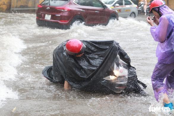 Dòng nước xiết khiến người dân ngã xe máy.