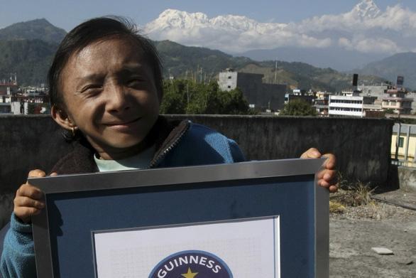 Khagendra Thapa Magar chụp ảnh cùng giấy chứng nhận kỷ lục Guinness gần ngọn núi Machchhapuchhre ở Pokhara, Nepal vào tháng 10-2010 - Ảnh: AFP