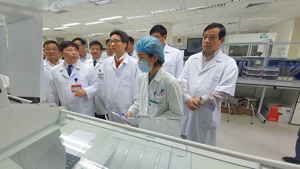 Phó Thủ tướng Vũ Đức Đam (thứ 3 từ phải) kiểm tra phương tiện xét nghiệm tại Bệnh viện Bệnh nhiệt đới Trung ương. Ảnh: BYT