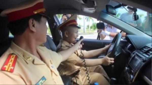 Cậu bé ngồi trong xe, rành rọt tuyên truyền giao thông cùng đại tá Lê Ngọc. (Ảnh: Motthegioi)