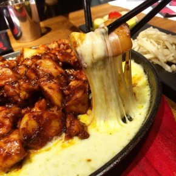 Trên chiếc chảo gang, lớp phô mai chảy ra bởi sức nóng của bếp điện, che lấp những miếng thịt gà vàng ươm, bóng nhẫy và dậy mùi thơm lừng.