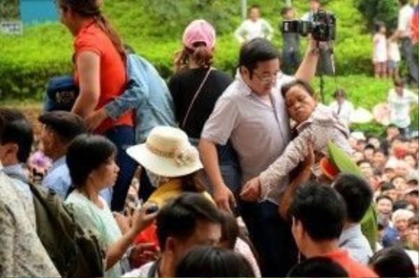 Người phụ nữ mặc áo chống nắng ngất xỉu trong đám đông, được cảnh sát dìu lên chỗ cao, cạnh nam thanh niên cầm máy ảnh, để lấy không khí thở, sau đó được đưa đến bộ phận y tế.